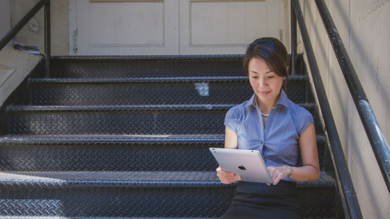 woman looking at ipad on steps