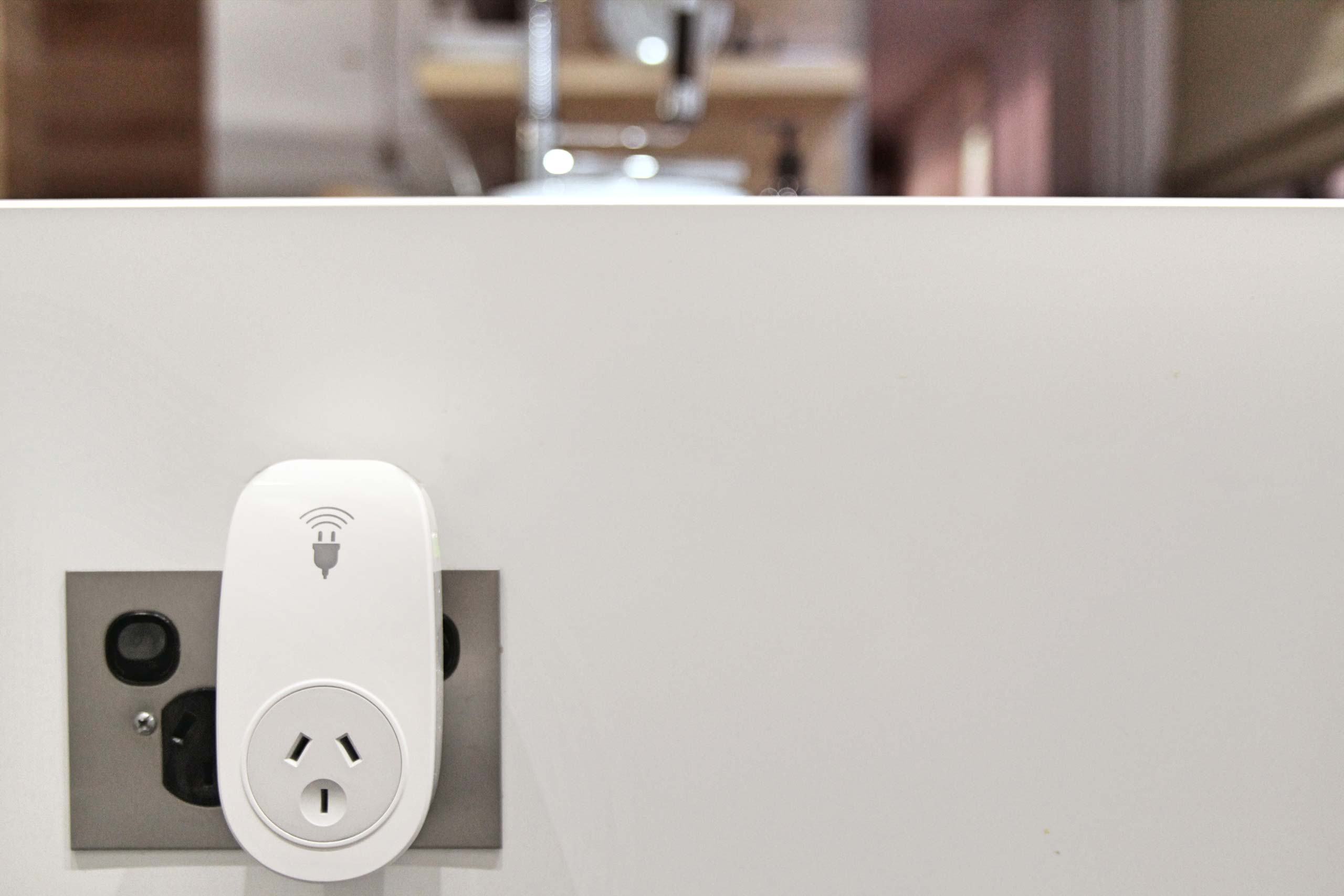 A smart plug is plugged into a modern, metal power point socket.