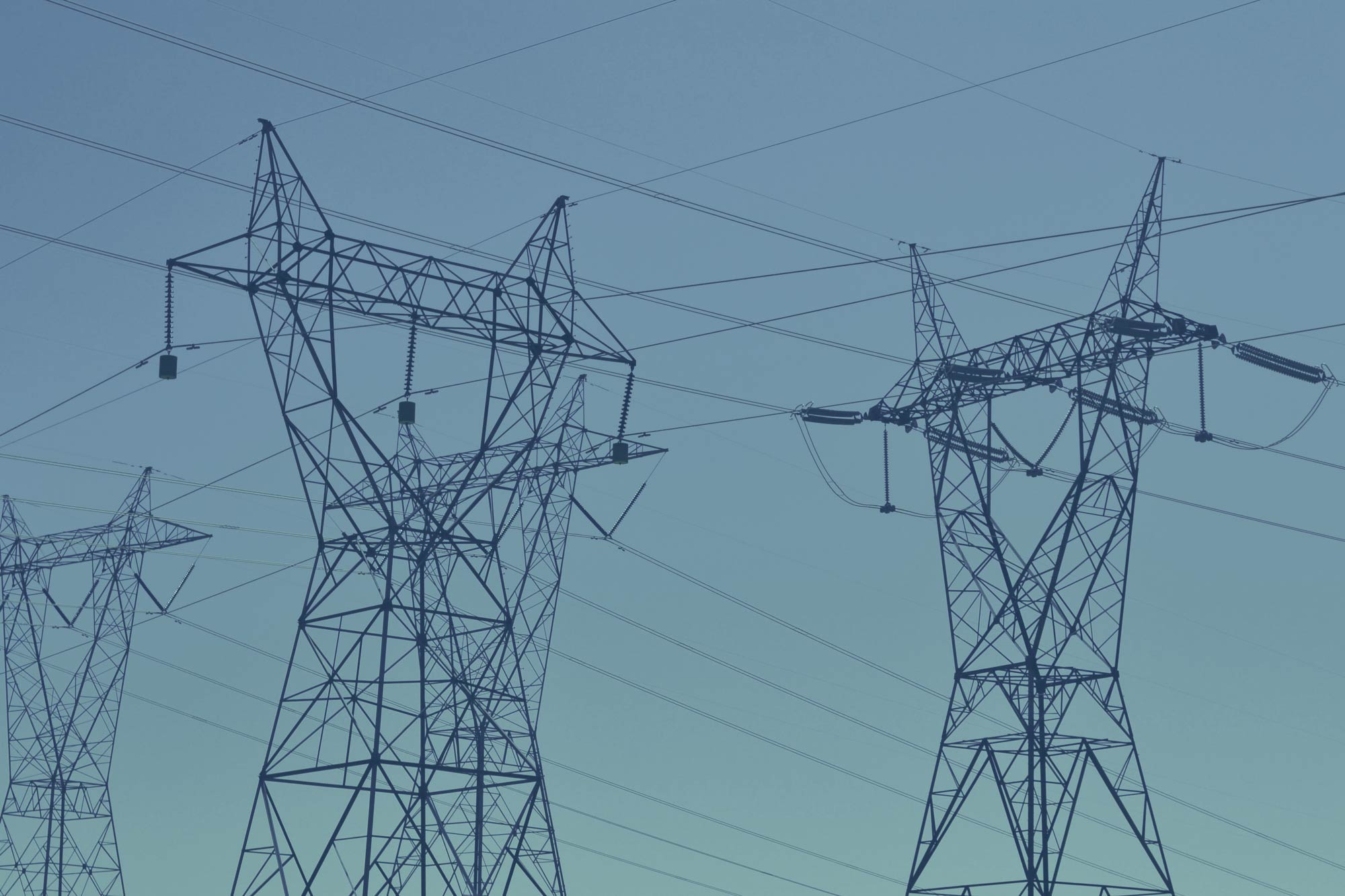 Two lines of large electricity towers powering the grid intersect, with clear blue skies in the background.