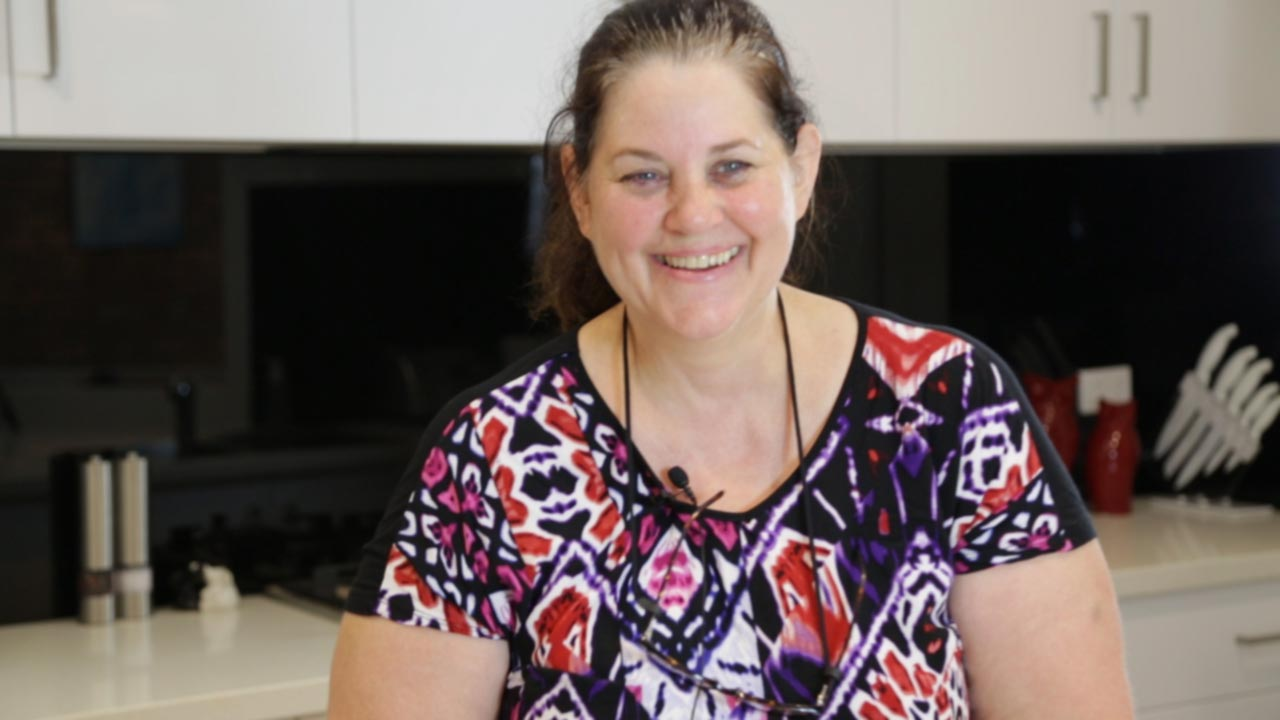 A middle aged Australian woman stands inside her modern home, smiling.