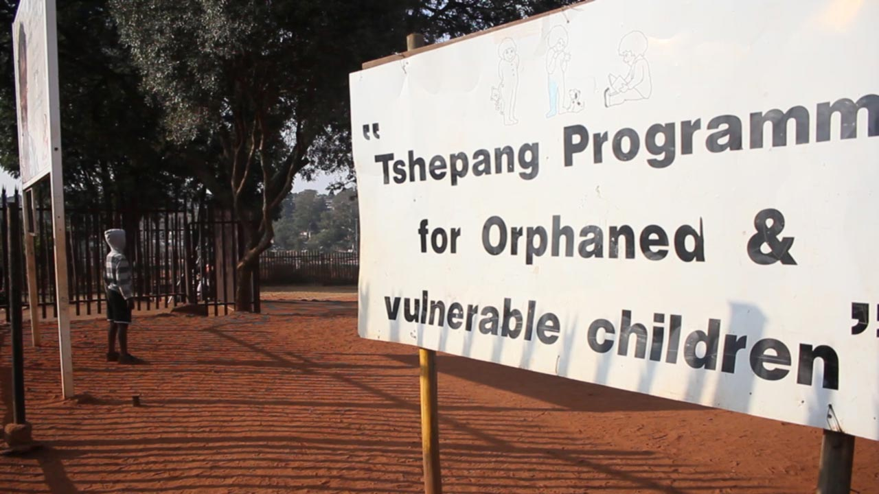 "A large white sign bathed in sunlight, saying ""Tsephang Orphanage"", stands proudly in the dark red African dirt."