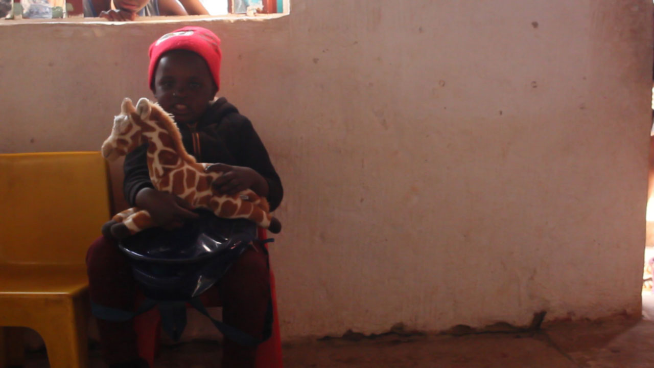 A small, young African boy sits indoors on a tiny plastic chair, holding tightly to his new stuffed toy giraffe.