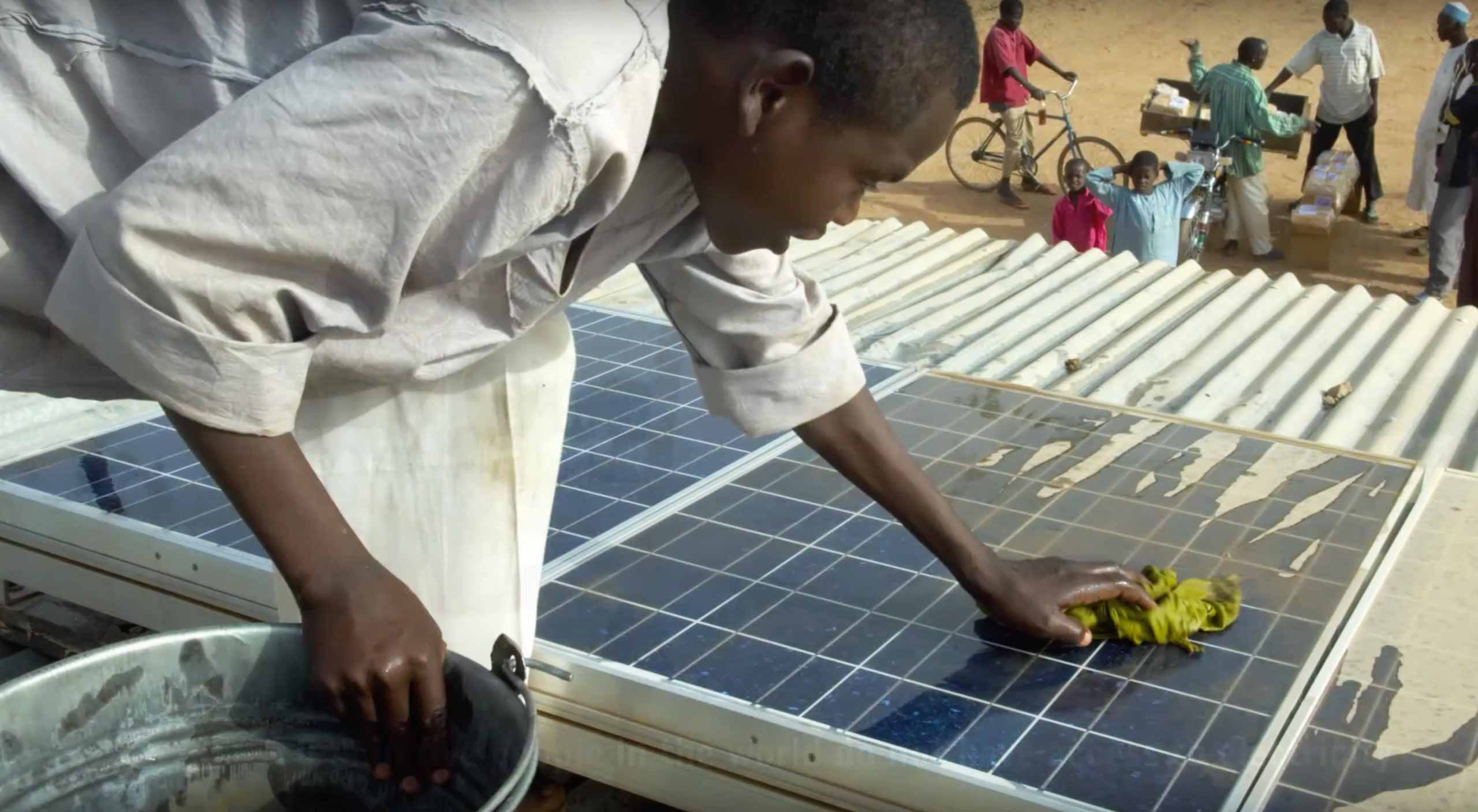 An African man cleans the solar panels atop one of the village's buildings by hand.