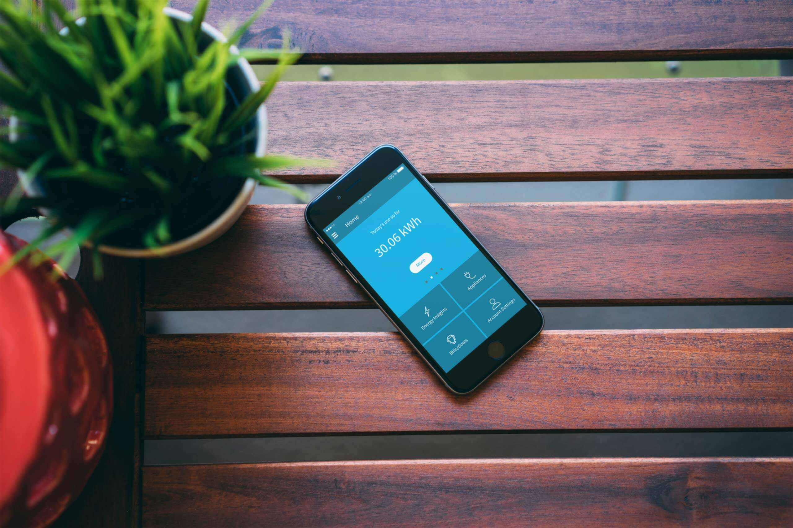 The carbonTRACK app is open on a phone sits on the dark, wooden slats of an outdoor table.
