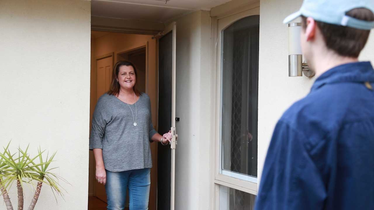 A happy and smiling home owner stands at the front door, welcoming in the carbonTRACK electrician ready to install her intelligent energy management system.