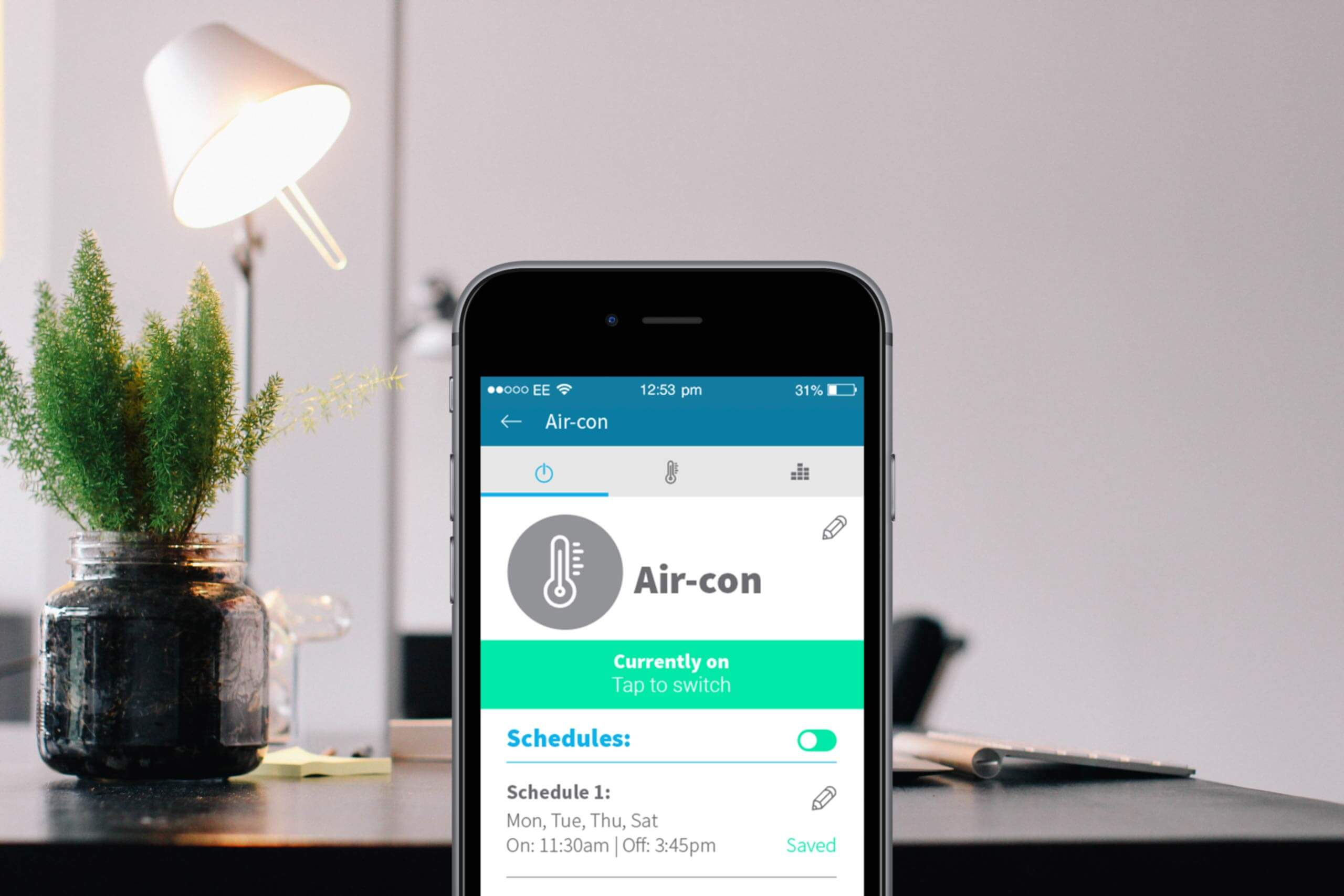 The carbonTRACK app open showing the ability to turn air conditioners on and off remotely, with the background of a bright, modern home interior.