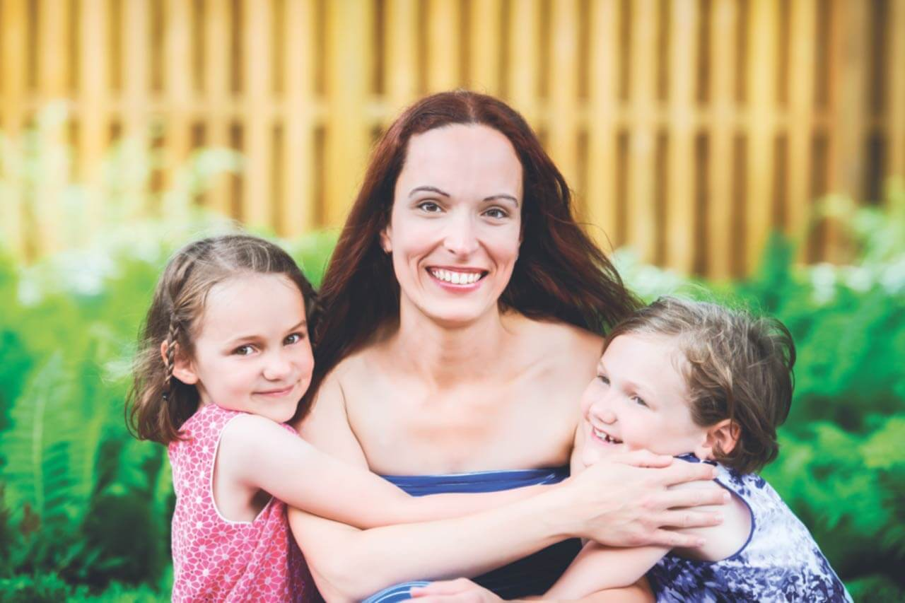 A young mother holds her two children as she smiles at the camera while outdoors.