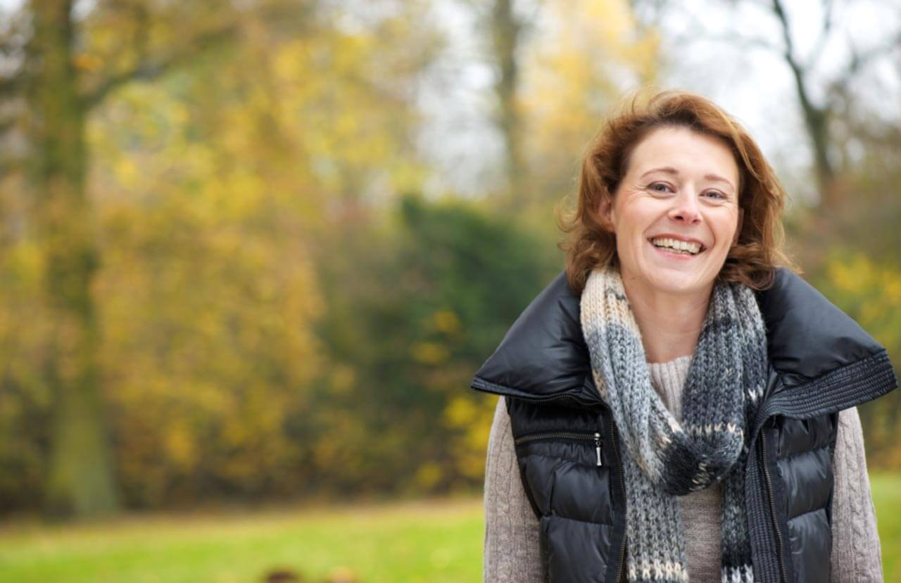 A middle aged woman smiles towards the camera in a autumn field.