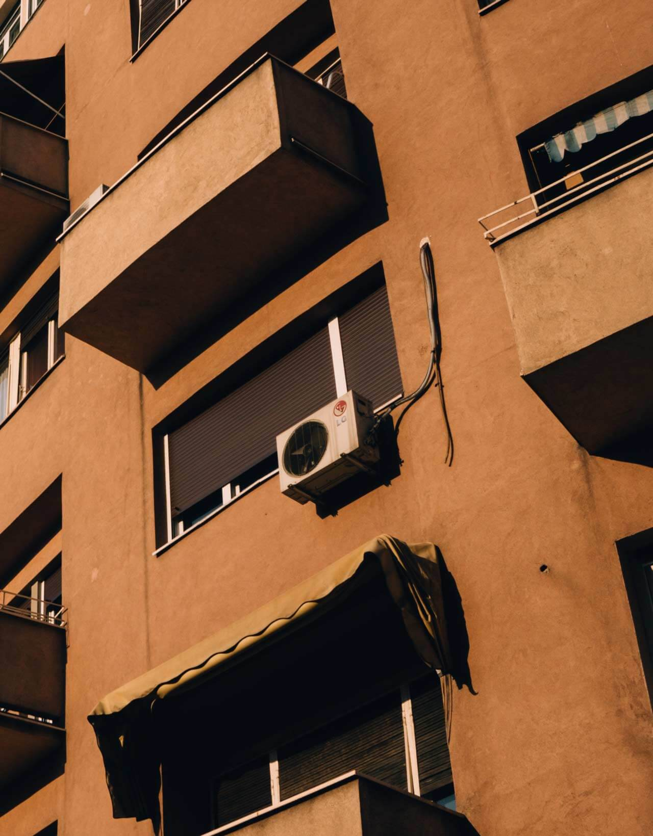 An old rustic brown apartment building with identical balconies lie contrast to a white air conditioner system hanging off the outside of the apartment.