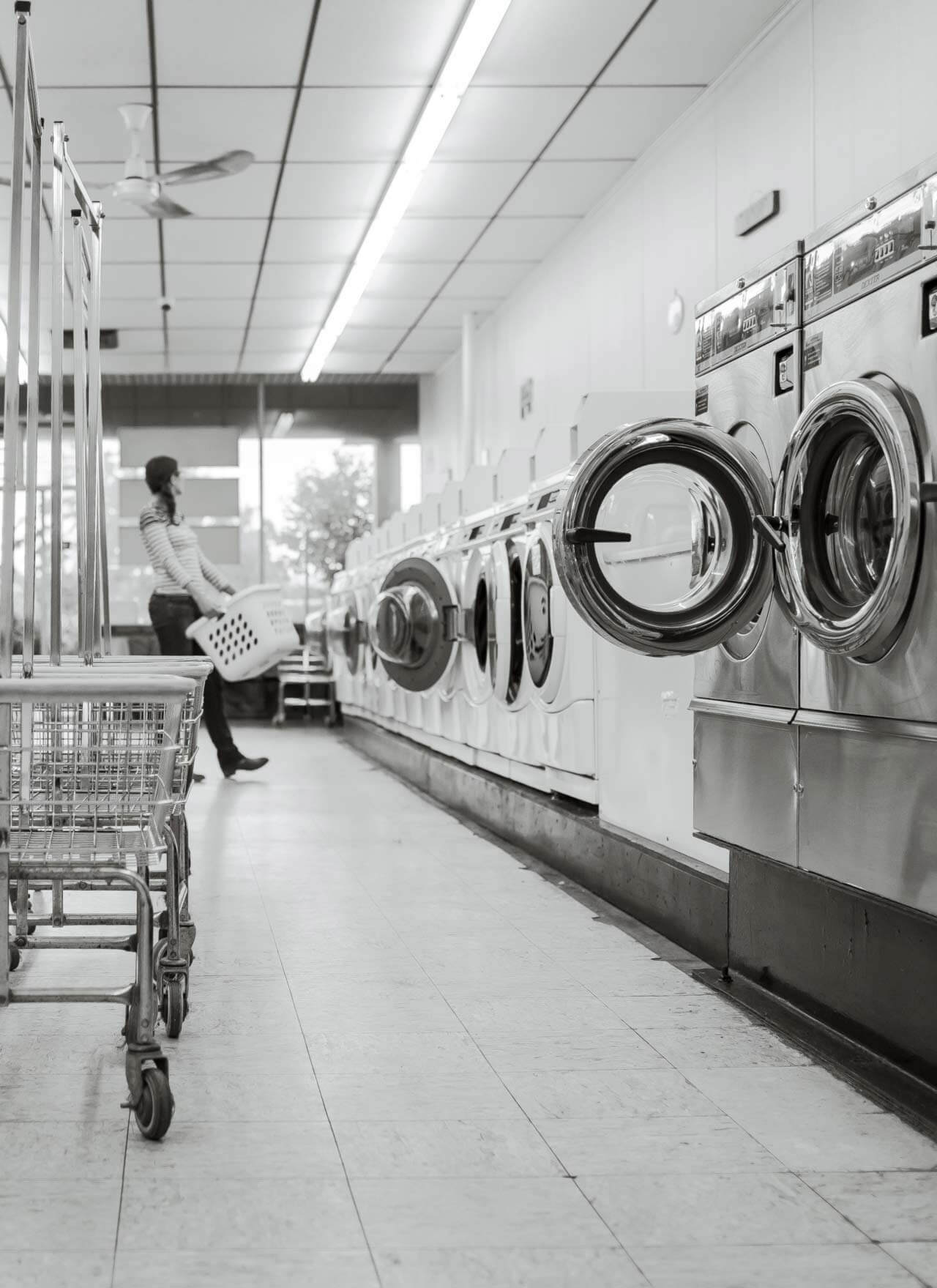 A woman carries a washing basket in the background of a Laundromat. Silver and white washing machines line the wall.