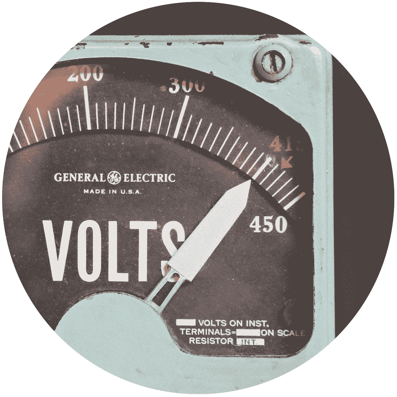 An old and worn, brown and white voltmeter's arrow points to 415 volts.