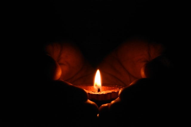 Two hands hold a small candle with an orange flame